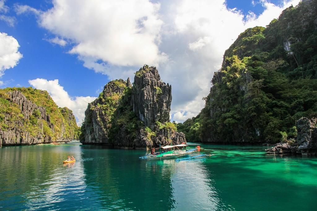 laguna con rocce e vegetazione e barca