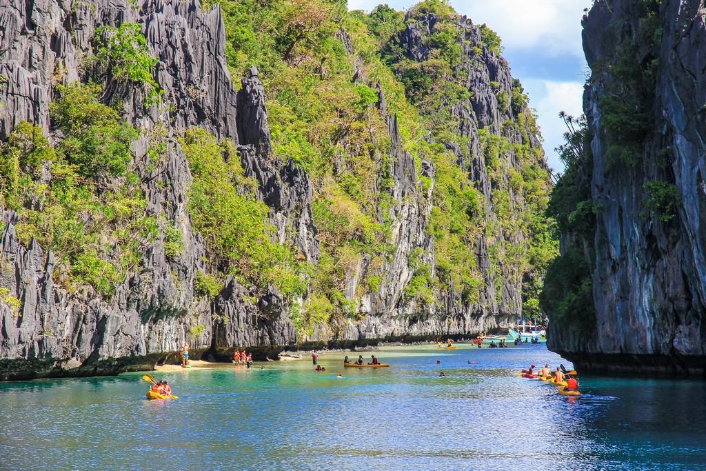 laguna con rocce e vegetazione e kayak