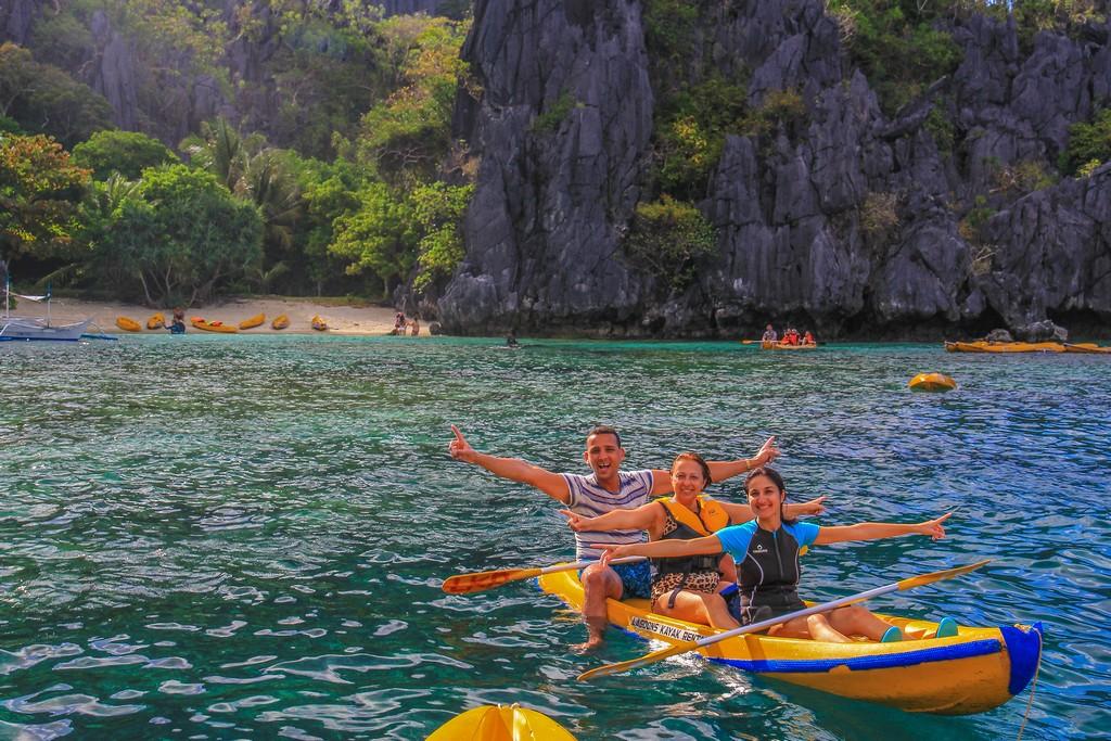 3 persone su kayak in mare con spiaggia dietro