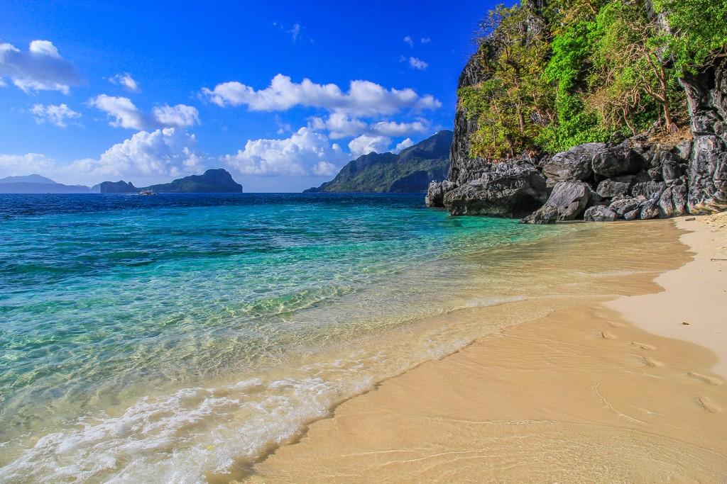 spiaggia con mare cristallino e montagne
