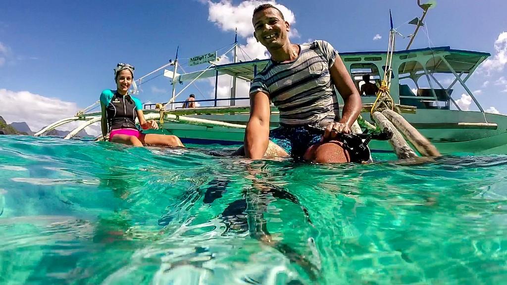 coppia in mare con barca dietro