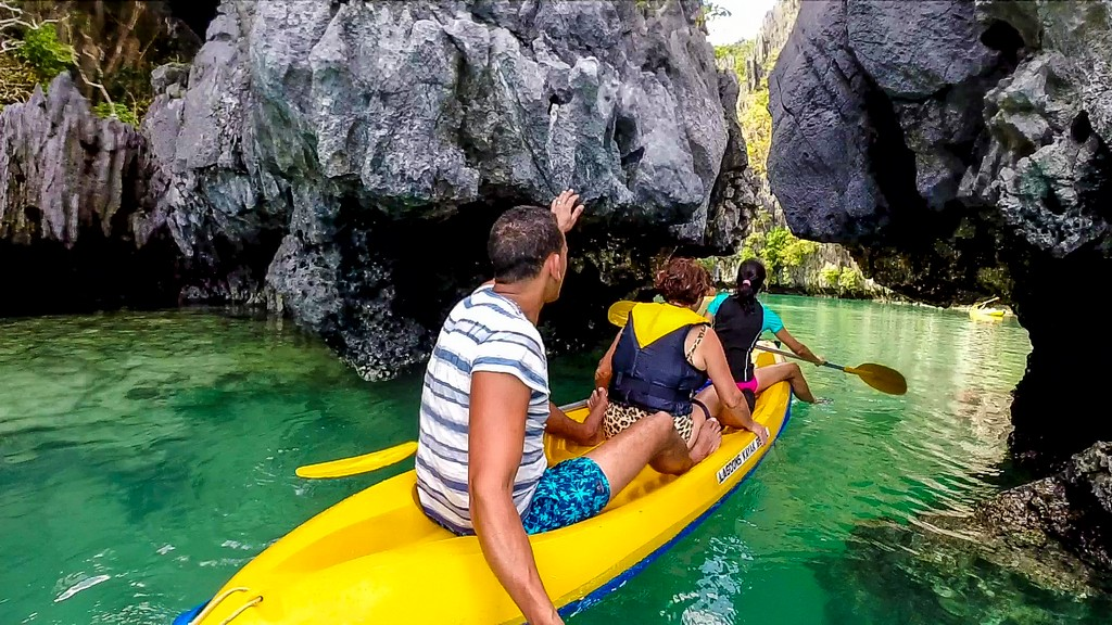 3 persone in kayak entrano in laguna chiusa da rocce
