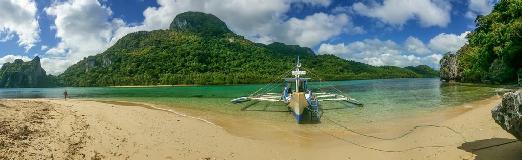 panorama di spiaggia con barca e montagna