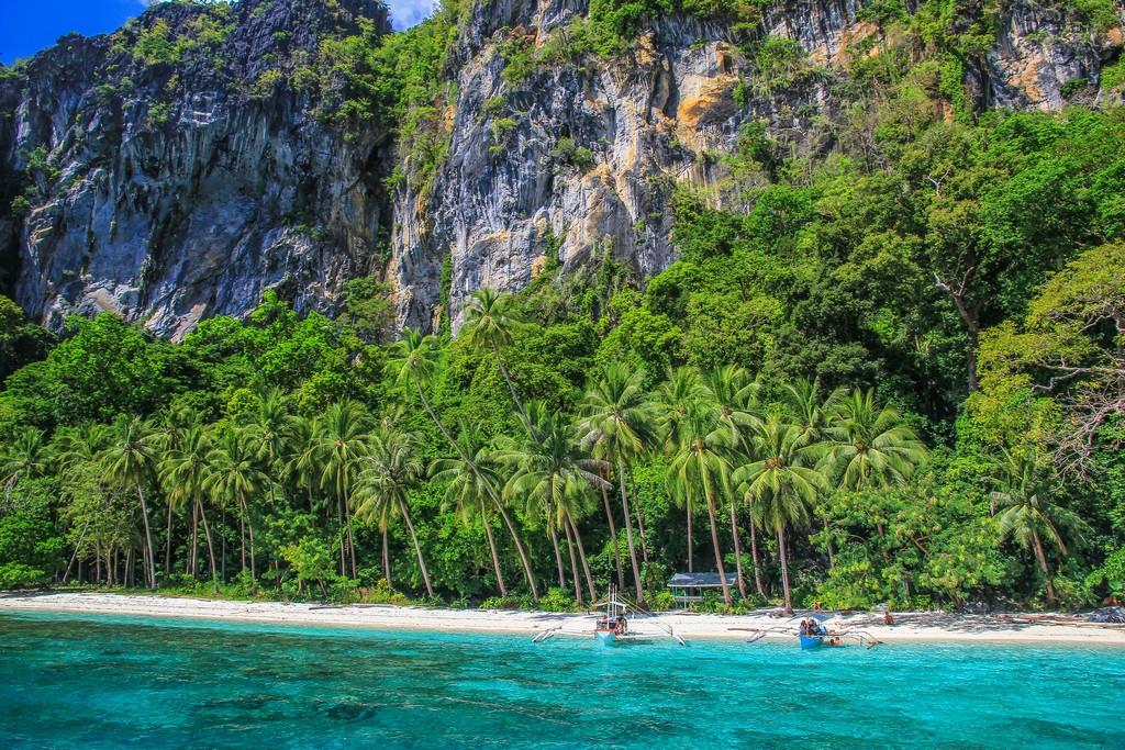 spiaggia con mare cristallino e montagne e barca