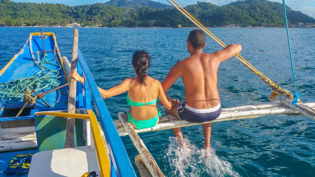 coppia sui passanti dei bilancieri di una barca in mare