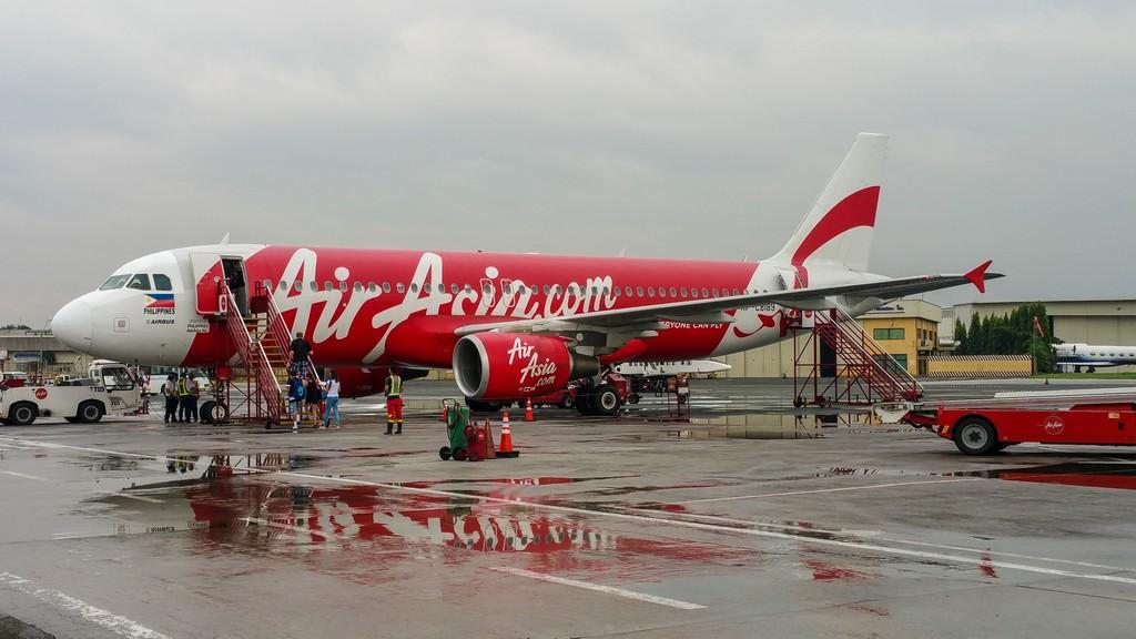 aereo di linea air asia in pista con pozzanghere