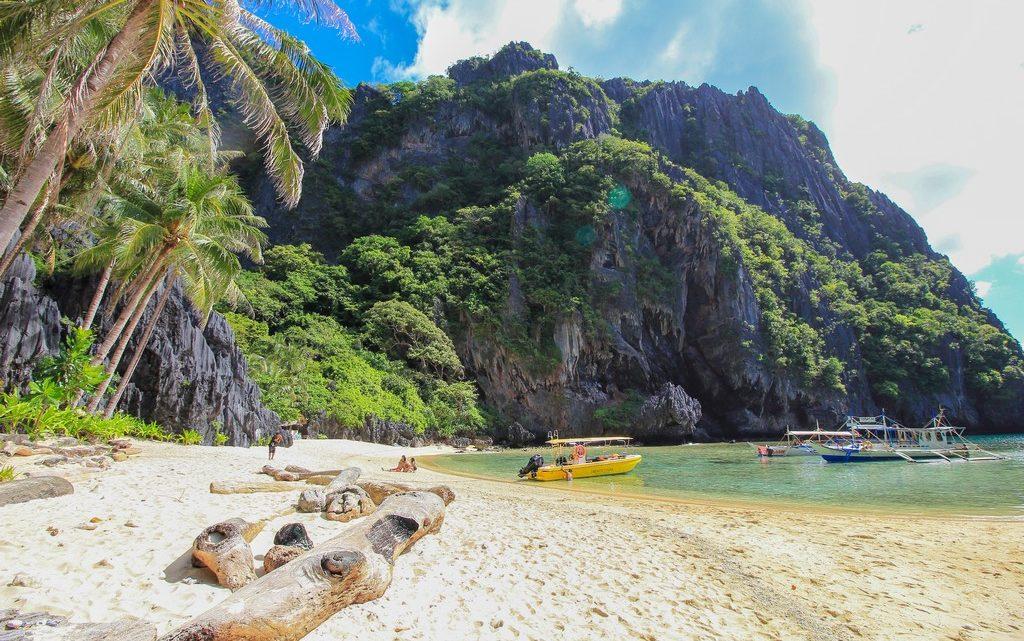 spiaggia bianca con tronchi barche e montagne