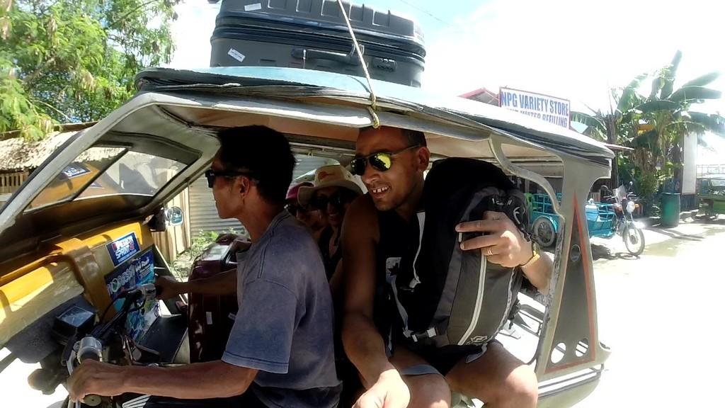 mototaxi con persone a bordo e valigia sul tetto