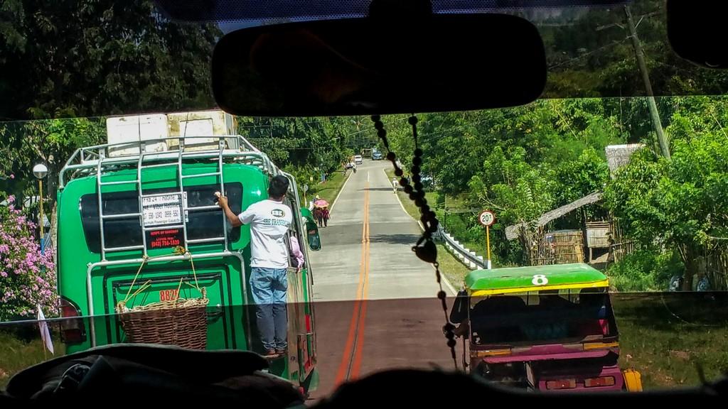 vista della strada e di mezzi visti dal cruscotto di un'auto