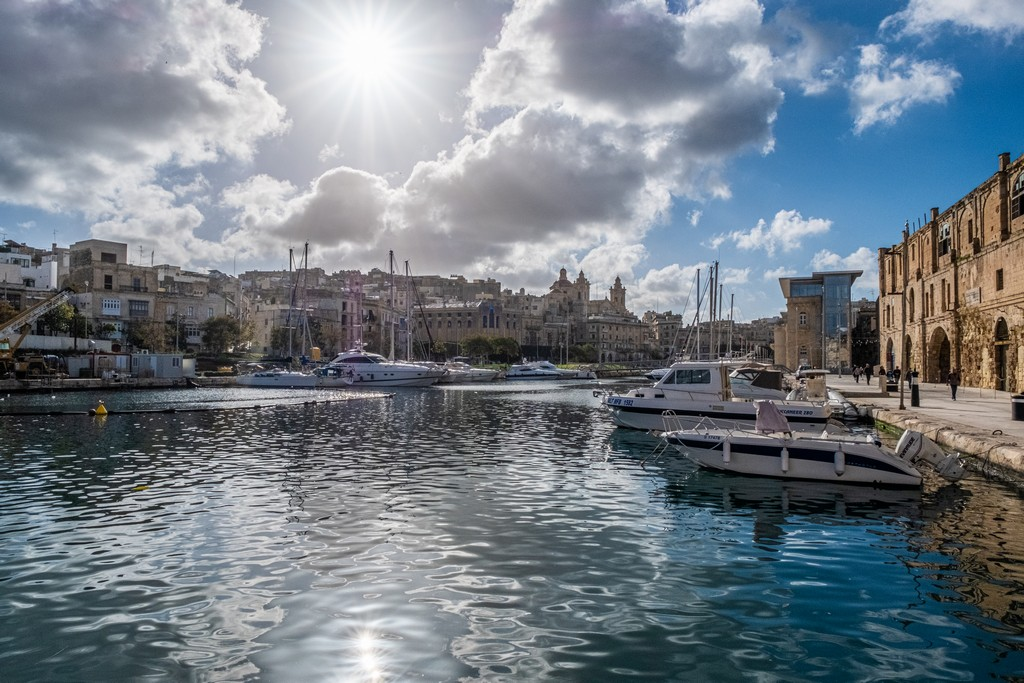 sole si specchia sul porto con barche
