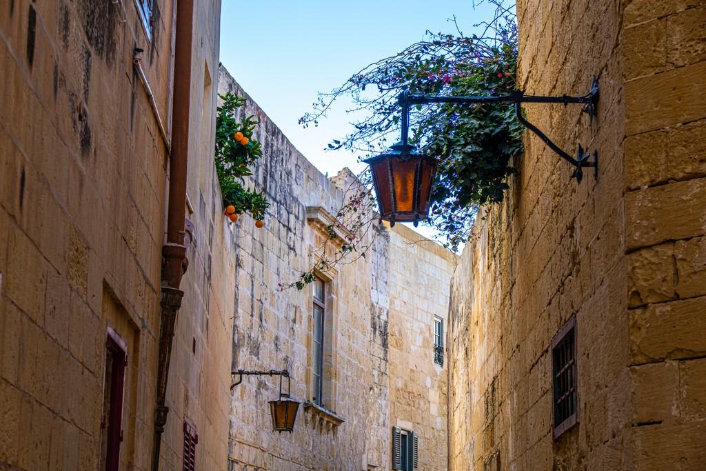Visita a Mdina vietta deserta con lampione e arance