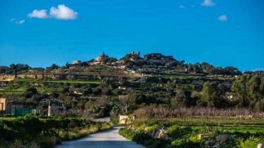 collina verde oltre la strada con cielo azzurro