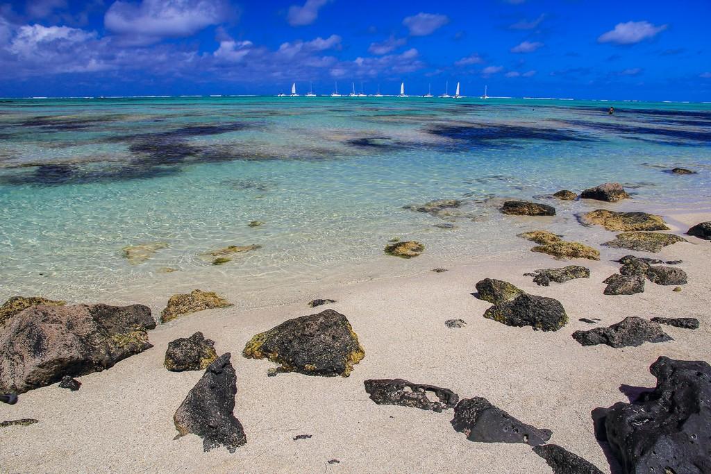spiagge con sabbia bianca massi e barchette in lontananza