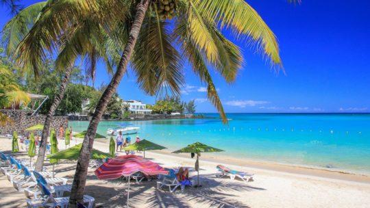 spiaggia di sabbia bianca e mare azzurro con palme e ombrelloni