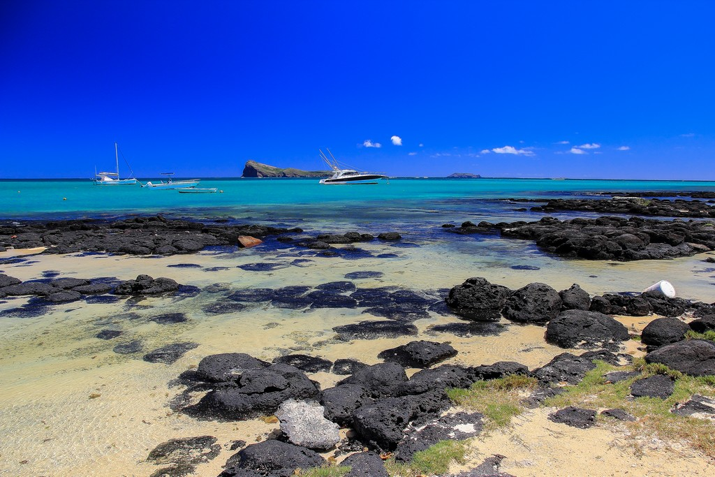spiaggia con massi neri barche e isole in lontananza