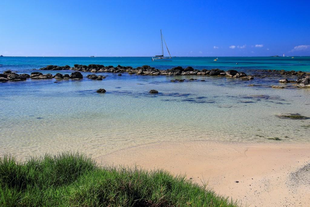 spiaggia con mare azzurro e sassi