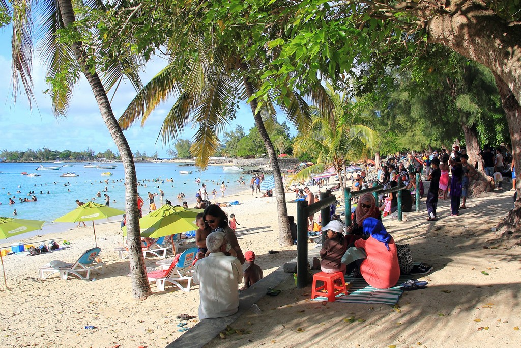 spiaggia con sabbia palme e molte persone