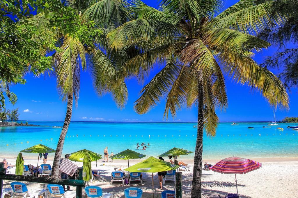 spiaggia con sabbia bianca ombrelloni e palme