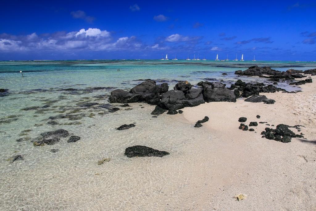 spiaggia con sassi neri e sabbia bianca