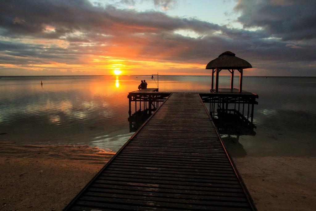 tramonto sul mare con pontile e persone sedute