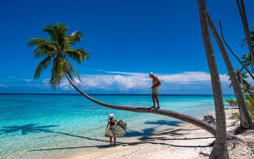 spiaggia con palme e coppia che si guarda