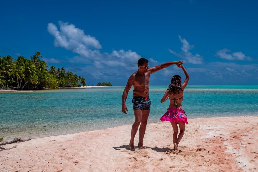 isola di sabbia rosa con palme e coppia che balla