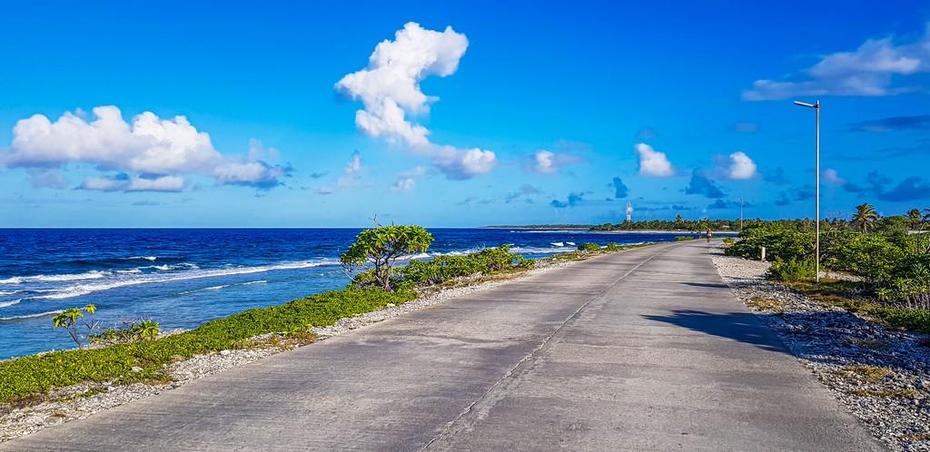 guida a Rangiroa,, strada con oceano a lato e nuvole