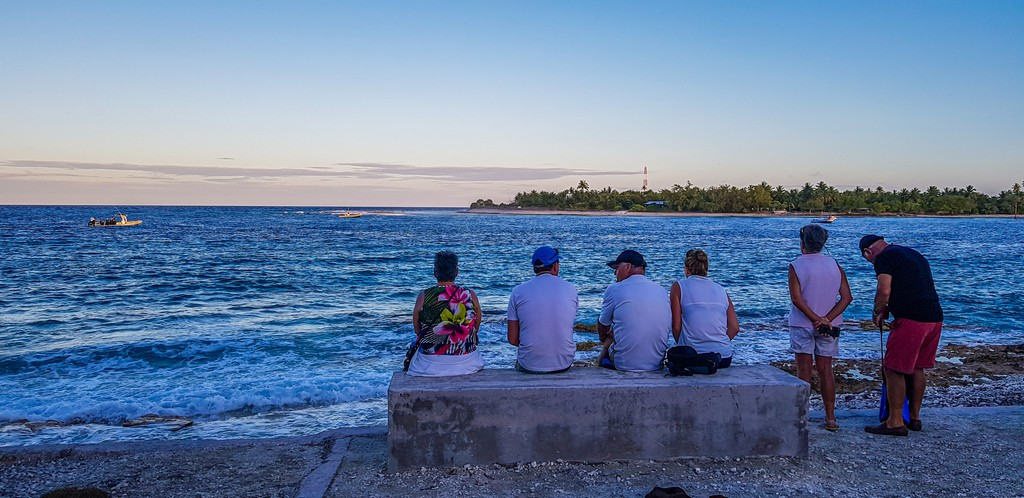 guida a Rangiroa, persone sedute davanti al mare al tramonto