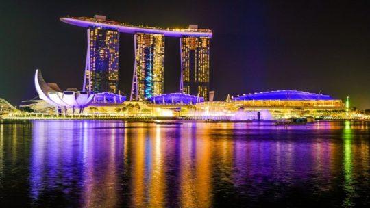 vista di un grattacielo a forma di nave con baia in primo piano di notte