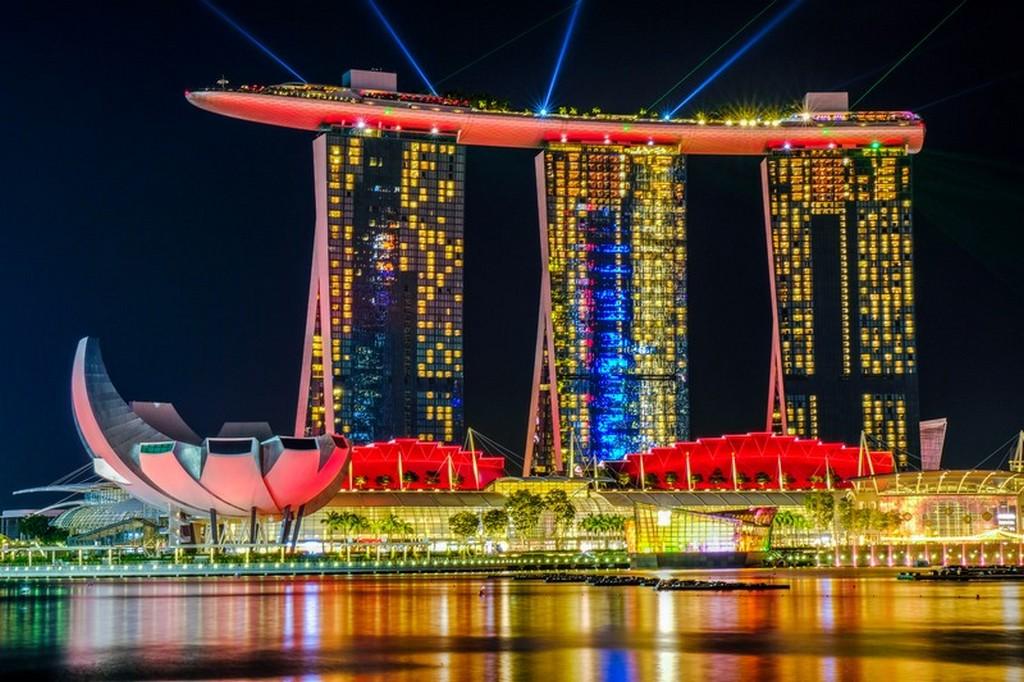vista di un grattacielo a forma di nave con baia in primo piano di notte e fasci di luce