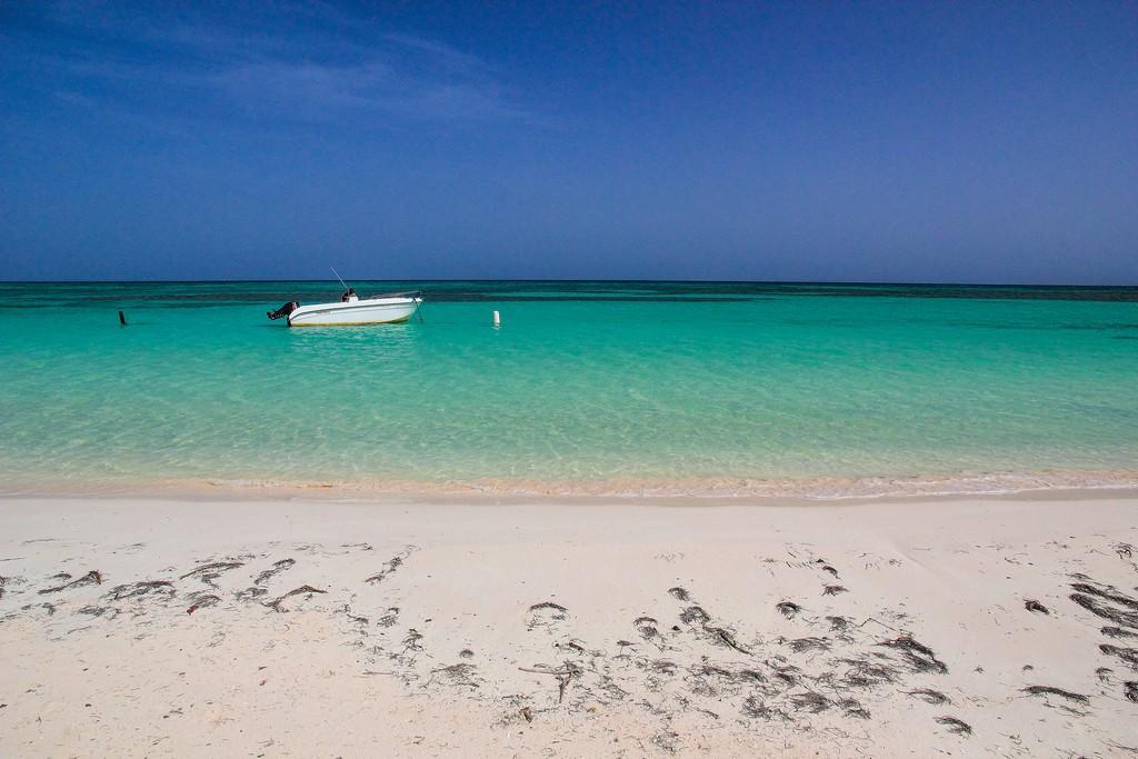 spiaggia di sabbia bianca con mare turchese e barca