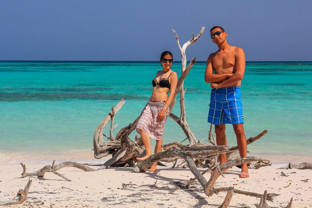 coppia in spiaggia di sabbia bianca con mare turchese e alberi secchi
