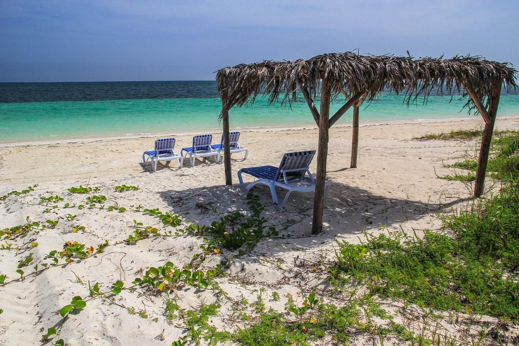 spiaggia di sabbia bianca con mare turchese sdraio e tettoia di paglia