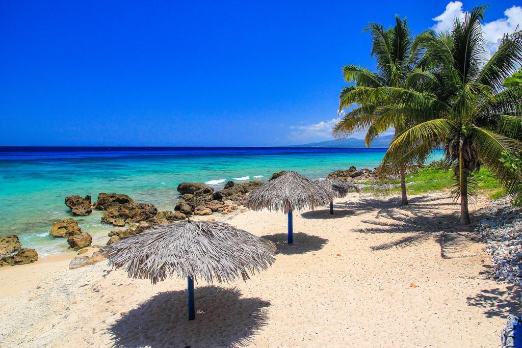 spiaggia di sabbia bianca con mare turchese ombrelloni di paglia e palme
