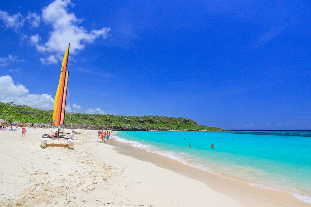 spiaggia di sabbia bianca con mare turchese e barca a vela