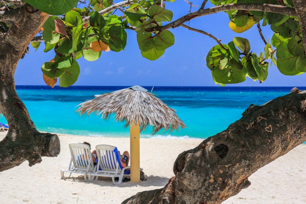 spiaggia di sabbia bianca con mare turchese con ombrellone e sdraio