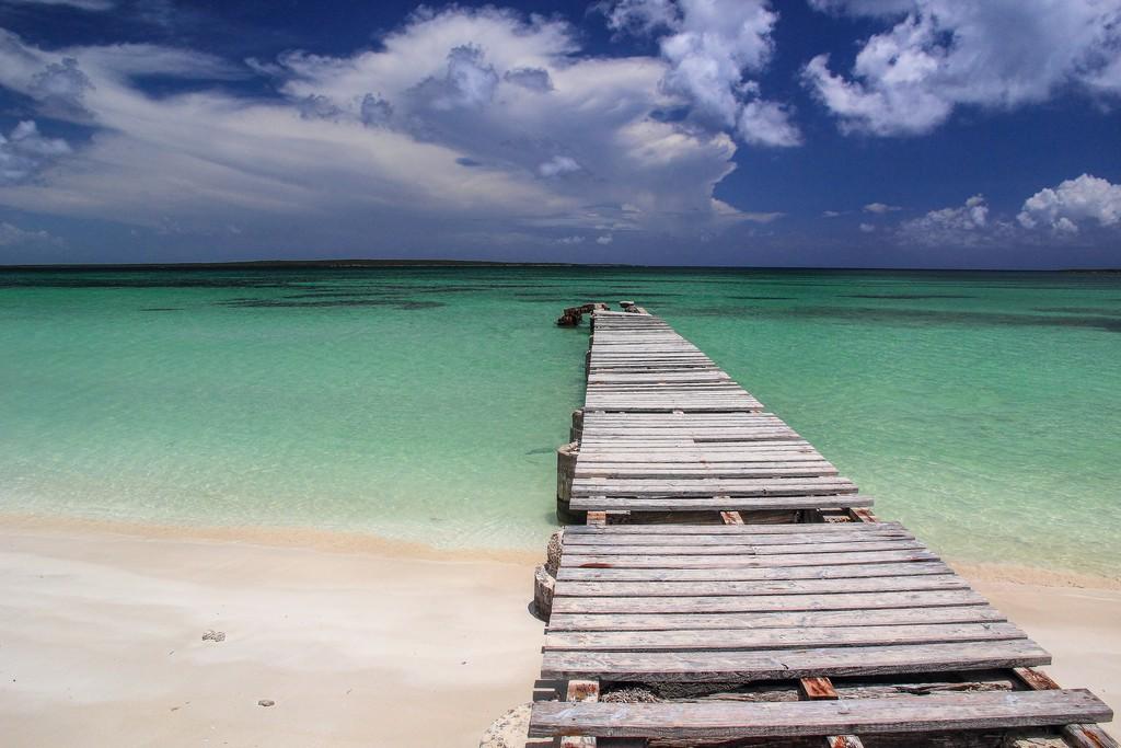 pontile antico di legno si protende verso spiaggia di sabbia bianca con mare turchese