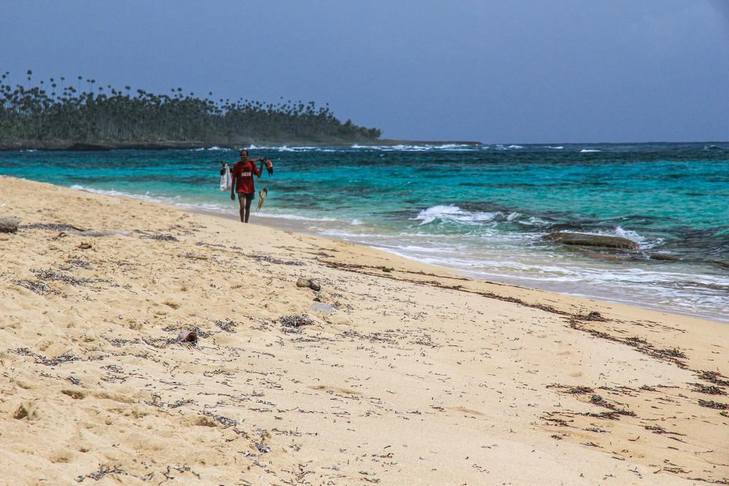 pescatore con pesci in spiaggia di sabbia bianca con mare turchese in lontananza