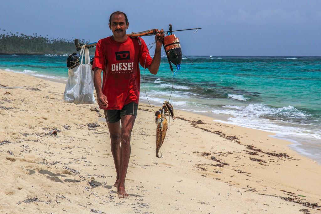 pescatore con pesci in spiaggia di sabbia bianca con mare turchese