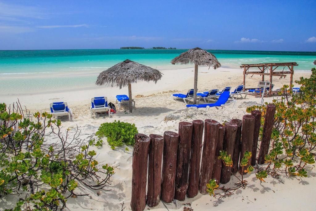 spiaggia di sabbia bianca con mare turchese sdraio e ombrelloni