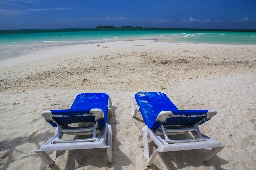 spiaggia di sabbia bianca con mare turchese e sdraio