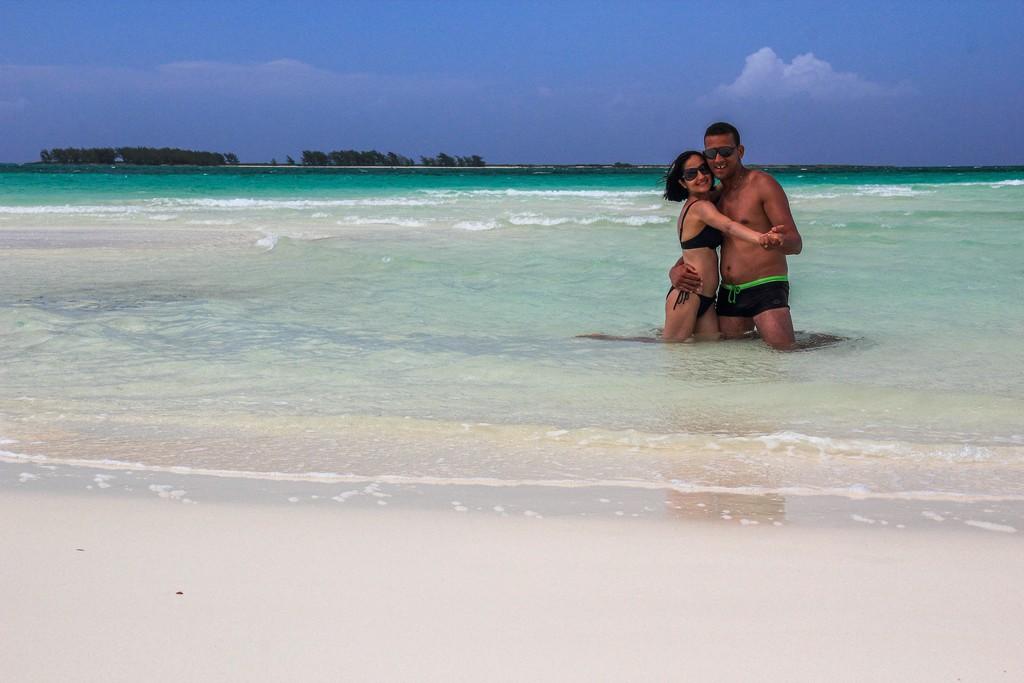 coppia in spiaggia di sabbia bianca con mare turchese con isola dietro