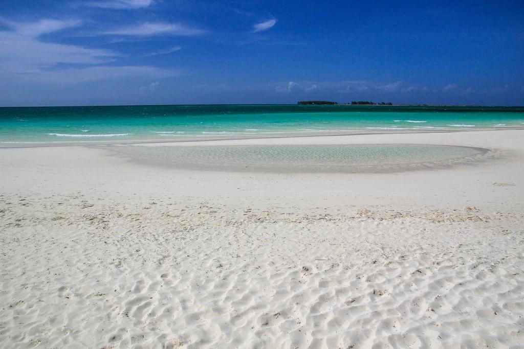 spiaggia di sabbia bianca con mare turchese e isole in fondo