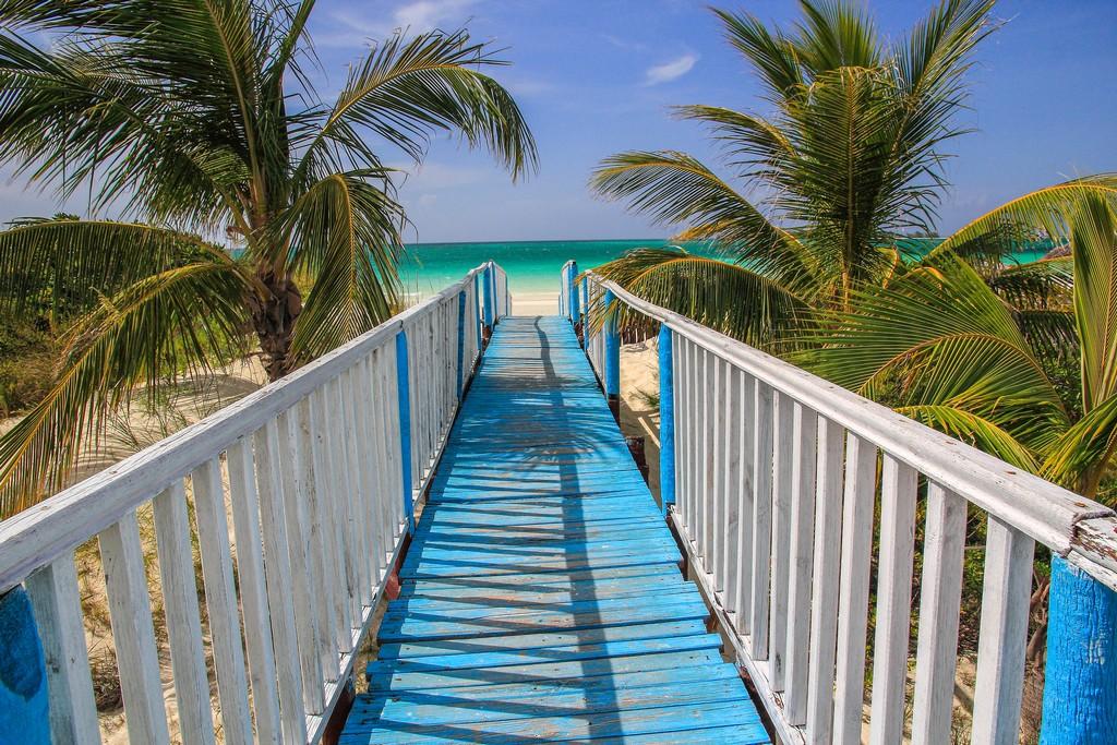 passerella azzurra e palme verso spiaggia di sabbia bianca con mare turchese