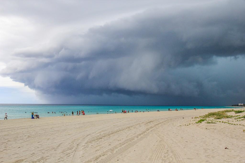spiaggia di sabbia bianca con mare turchese con nuvola temporalesca
