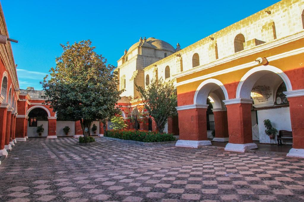 Guida ad Arequipa ampio cortile con pavimento a scacchi e portici rossi