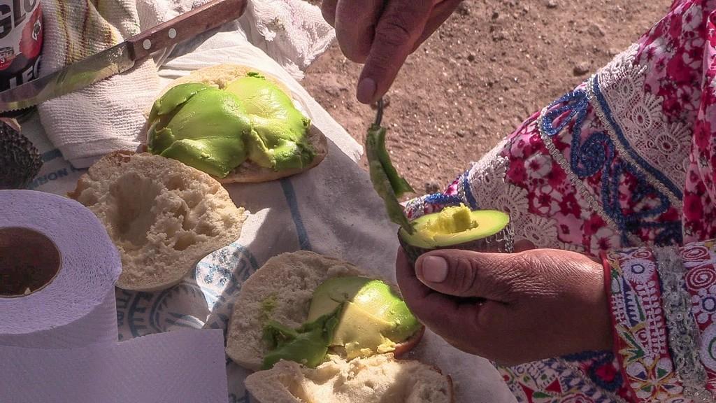 donna prepara un panino con avocado in strada