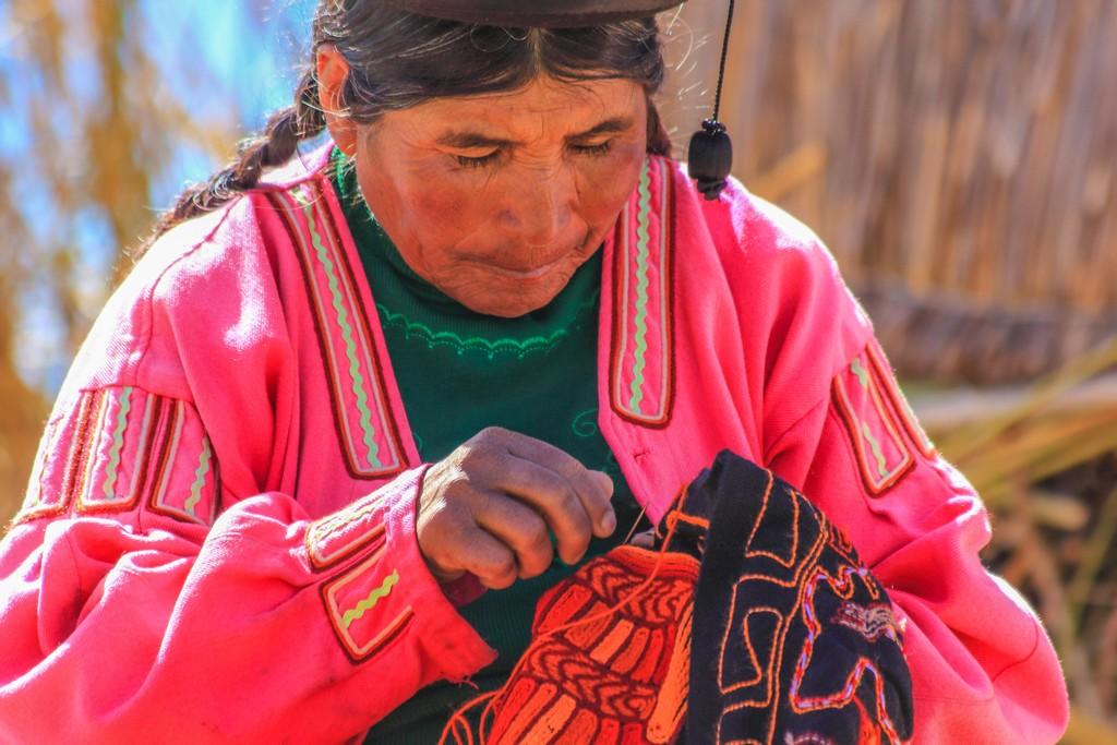donna che ricama in abiti colorati