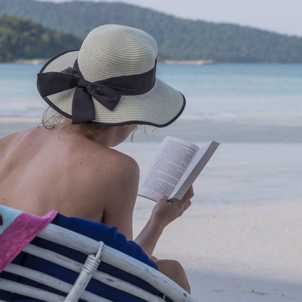 donna legge un libro in spiaggia