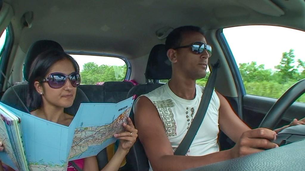 uomo al volante e donna guarda mappa